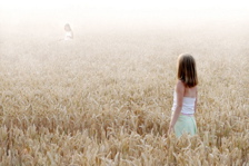 Image: Young girl standing in a golden wheat field, looking out at her astral body.